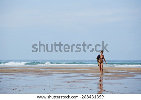 Full length portrait of young sexy woman in bikini walking down wet sand reflecting blue sky light at sunny day, seductive woman in swimsuit walking on the beach wit copy space sky - stock photo