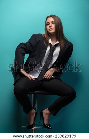 Full length portrait of young sexy woman wearing men suit oversize and tie holding jacket behind  her back, provocative look, interior shot - stock photo