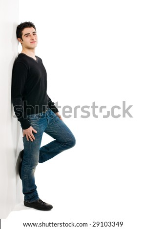Full length portrait of young smiling man standing against white wall with copy space for your text - stock photo