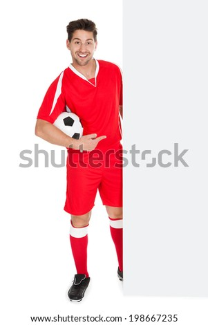 Full length portrait of young soccer player with football pointing at billboard over white background - stock photo