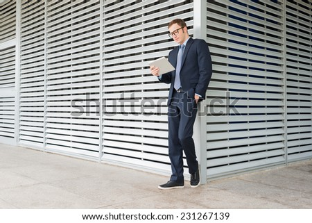 Full-length portrait of young stylish businessman reading something on the digital tablet - stock photo
