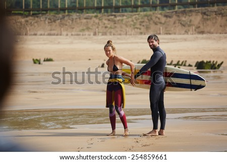 Full length portrait of young surfer couple having fun and fool around while looking to the camera, professional surfer guy and girl relaxing on the beach at sunny day - stock photo