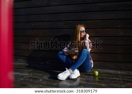 Full length portrait of young university student in sunglasses with smart phone in hands sitting on wooden surface outdoors, stylish teenager using mobile phone while sitting at university campus - stock photo