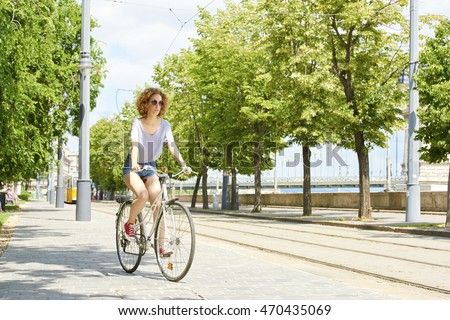 Full length portrait of young woman cycling through the city.