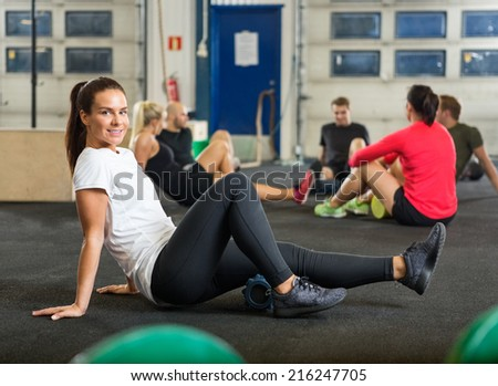 Full length portrait of young woman exercising in cross fitness box - stock photo