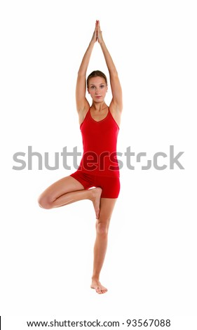 Full-length portrait of young woman in tree position during yoga practice, isolated over white - stock photo