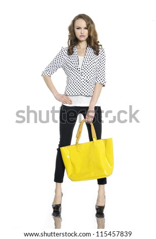 Full length portrait of young woman posing with yellow bag on white background - stock photo