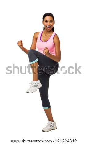 Full length portrait of young woman practicing Zumba dance against white background. Vertical shot. - stock photo