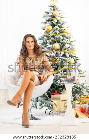 Full length portrait of young woman sitting near christmas tree - stock photo