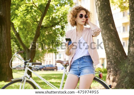 Full length portrait of young woman standing by her bike and using cellphone while listening music in th park.