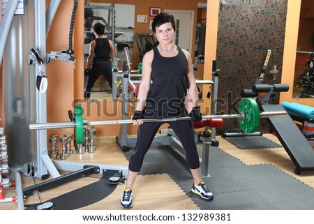 Full length portrait of young woman with barbell