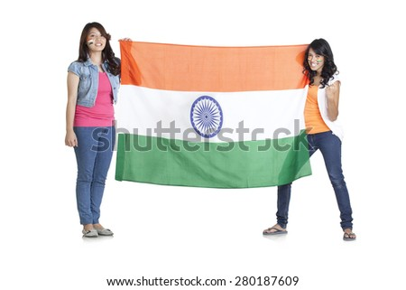Full length portrait of young women in casuals holding Indian flag over white background - stock photo