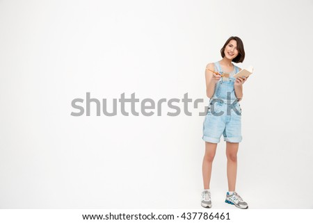 Full length portrait pretty girl, in gray shirt and denim overall, making notes,  pointing forward with finger, isolated on white background - stock photo