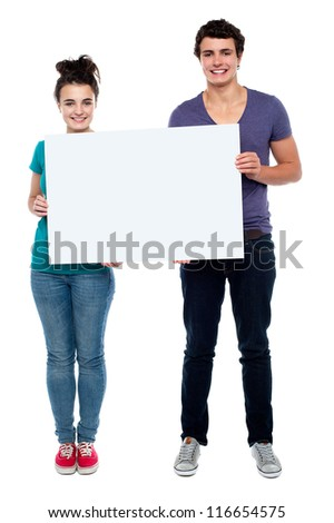 Full length portrait teen couple posing with blank billboard - stock photo