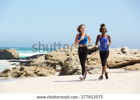 Full length portrait two young women running on the beach
