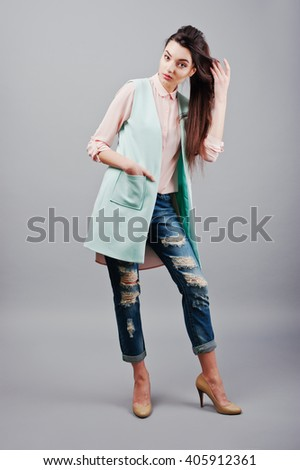 Full-length portrait young brunette girl wearing in pink blouse, turquoise jacket, ripped jeans and cream shoes .Fashion studio shot