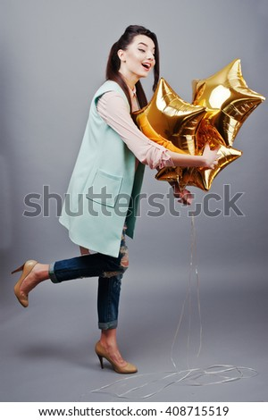 Full-length portrait young brunette girl wearing in pink blouse, turquoise jacket, ripped jeans and cream shoes holding gold star balloons.Fashion studio shot - stock photo