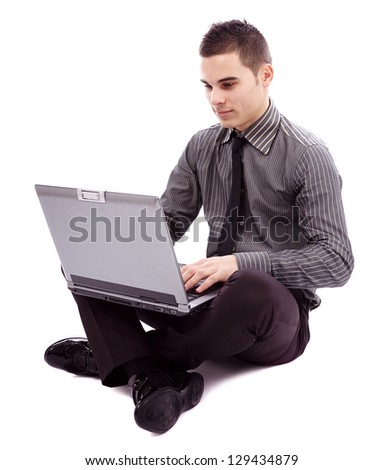Full length pose of young businessman sitting on the floor and writing on his laptop, isolated on white background - stock photo