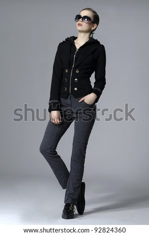 full length pretty woman with slim pose on black background dressed in style black dress
