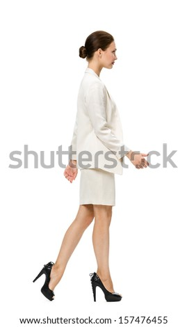 Full-length profile of walking business woman, isolated on white background. Concept of leadership and success - stock photo