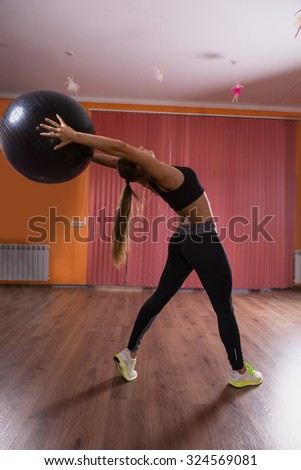 Full Length Profile of Young Woman Wearing Exercise Clothing Stretching Backwards and Holding Inflatable Exercise Ball Overhead in Dance Studio with Hardwood Floors