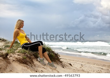 Full length profile portrait of a young woman sitting on a grassy bluff on the beach. She is staring out at the sea with a serious expression. Horizontal shot. - stock photo