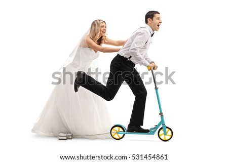 Full length profile shot of a bride pushing a groom on a scooter isolated on white background