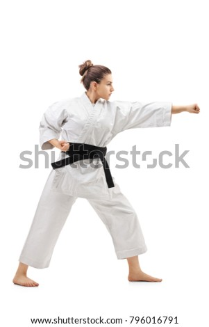 Full length profile shot of a karate girl punching isolated on white background