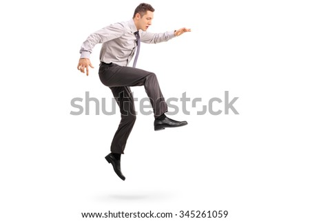 Full length profile shot of a young businessman jumping in the air shot in mid-air isolated on white background - stock photo