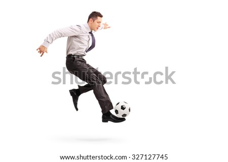 Full length profile shot of a young businessman kicking a football isolated on white background - stock photo