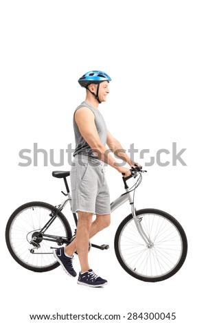 Full length profile shot of an active young man with a blue sports helmet on his head pushing a bike and smiling isolated on white background