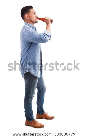 Full length profile view of a young Hispanic man drinking beer from a bottle against a white background - stock photo