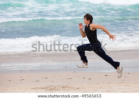 Full length profile view of a young man running in the surf on the beach. Horizontal shot. - stock photo