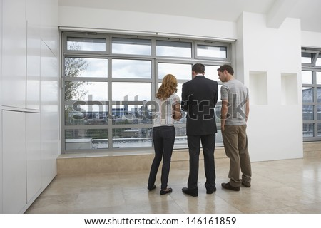 Full length rear view of a real estate agent showing couple new apartment - stock photo