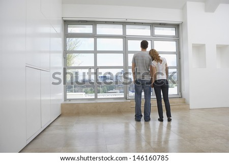 Full length rear view of an affectionate couple looking out of window in empty apartment - stock photo