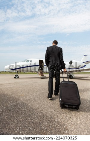 Full length rear view of businessman with luggage walking towards private jet - stock photo