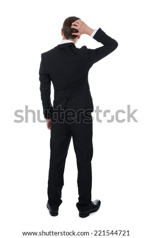 Full length rear view of confused businessman scratching his head over white background - stock photo