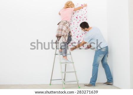 Full-length rear view of couple applying wallpaper to wall - stock photo