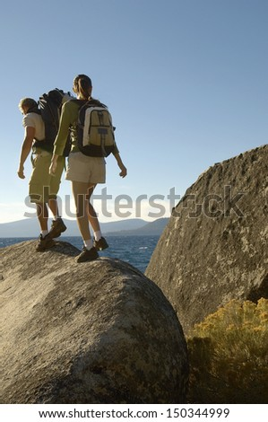 Full length rear view of hiking couple walking on boulder at coast