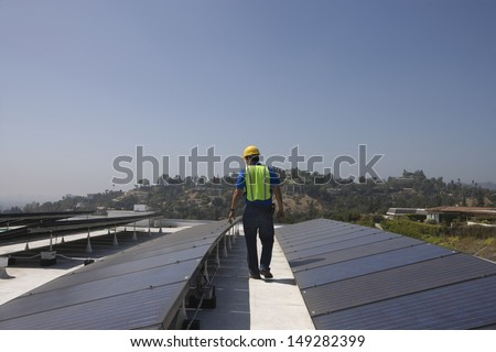 Full length rear view of maintenance worker inspecting solar panels on rooftop - stock photo