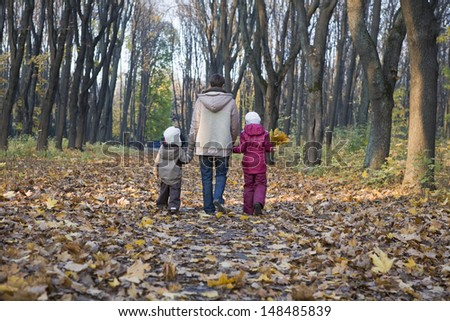 Full length rear view of mother and children walking in the park - stock photo