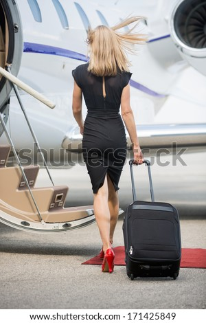 Full length rear view of rich woman with luggage walking towards private jet at airport terminal - stock photo