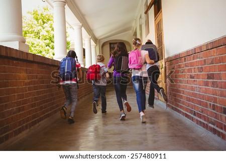 Full length rear view of school kids running in school corridor - stock photo