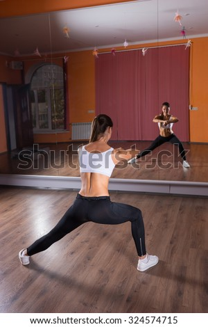 Full Length Rear View of Young Brunette Woman Wearing Exercise Clothing and Stretching Arms and Legs in Dance Studio While Looking at Reflection in Mirrors - stock photo