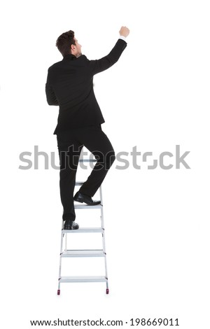 Full length rear view of young businessman climbing career ladder over white background - stock photo