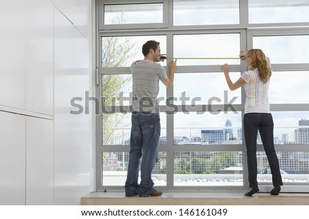 Full length rear view of young couple measuring window in modern apartment - stock photo