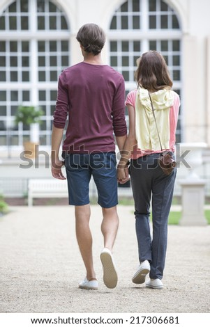 Full-length rear view of young couple walking against building - stock photo
