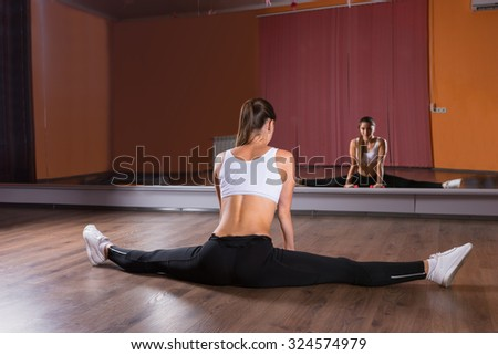 Full Length Rear View of Young Woman in Exercise Clothing Stretching Legs in Splits Pose in Dance Studio and Looking at Reflection in Mirrored Wall - stock photo