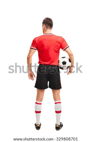 Full length rear view shot of a young football player in red jersey holding a ball isolated on white background - stock photo