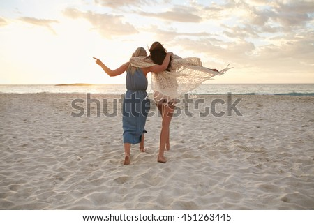 Full length rear view shot of two woman friends walking together on the beach. Female friends taking a walk on the sea shore and having fun.